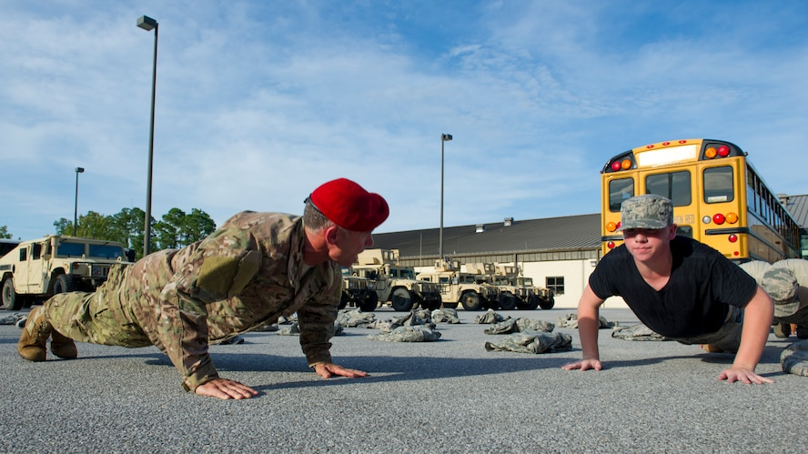 Retired Col. Kenneth Rodriguez, director of Junior ROTC Summer Leadership School, motivates a cadet while doing push-ups at Hurlburt Field, Fla., June 26, 2017. More than 60 JROTC cadets from five local high schools engaged in a variety of team-building and leadership skill-developing exercises during a Summer Leadership School trip to Hurlburt Field, June 26 – 30. (U.S. Air Force photo by Staff Sgt. Victor J. Caputo)