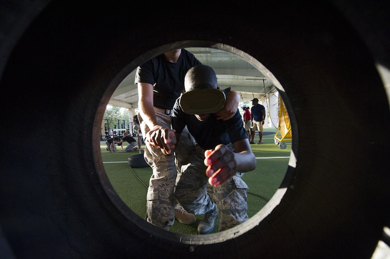 A blindfolded Junior ROTC cadet is guided through a tire at the end of an obstacle course at the Special Tactics Training Squadron, Hurlburt Field, Fla., June 26, 2017. Cadets had to maneuver through a tightly-constricted obstacle course while guiding blindfolded wingmen and carrying a variety of heavy objects, including weights and a training dummy on a stretcher. (U.S. Air Force photo by Staff Sgt. Victor J. Caputo)