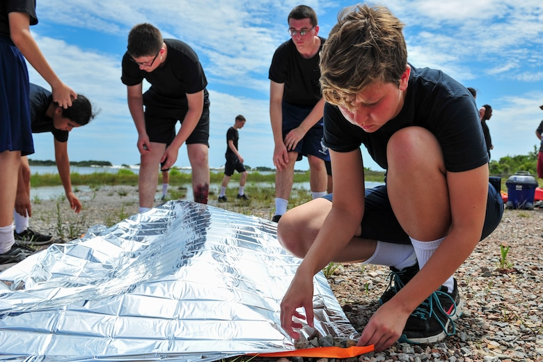 A Junior ROTC cadet anchors down a reflective blanket to make a rescue signal during survival, evasion, resistance and escape training at Hurlburt Field, Fla., June 29, 2017. SERE specialists with the 1st Special Operations Support Squadron gave Summer Leadership School cadets a crash course on SERE, including signaling aircraft, starting fires with natural resources, and crafting shelters in the wilderness. (U.S. Air Force photo by Staff Sgt. Victor J. Caputo)