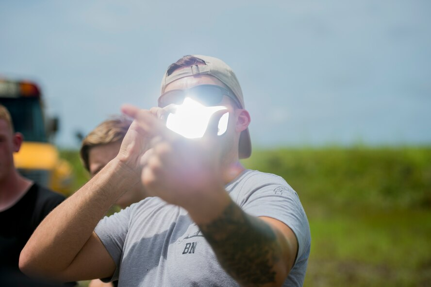 Senior Airman Heath Jolley, a survival, evasion, resistance and escape specialist with the 1st Special Operations Support Squadron, demonstrates how to signal with a mirror during SERE water survival training at Hurlburt Field, Fla., June 29, 2017. More than 50 cadets from five local high schools attended the Summer Leadership School at Hurlburt Field, where they learned about leadership, teamwork and life in the military. (U.S. Air Force photo by Staff Sgt. Victor J. Caputo)