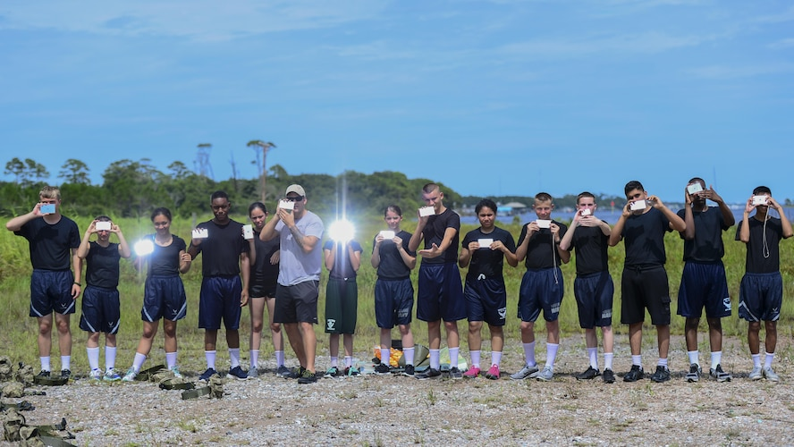 Junior ROTC cadets practice mirror signaling during survival, evasion, resistance and escape training at Hurlburt Field, Fla., June 29, 2017. SERE specialists with the 1st Special Operations Support Squadron gave Summer Leadership School cadets a crash course on SERE, including signaling aircraft, starting fires with natural resources, and crafting shelters in the wilderness. (U.S. Air Force photo by Staff Sgt. Victor J. Caputo)