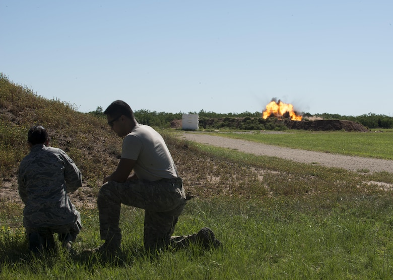 U.S Air Force Senior Airman Jason Jordan (right), 7th Civil Engineer Squadron explosive ordnance disposal journeyman assists an Airman from the 7th Operations Support Squadron (left) in setting off an explosive during a training exercise at Dyess Air Force Base, Texas, June 28, 2017. The EOD team often works closely with other first responders, such as: emergency management, security forces and the fire department to ensure any threats are eliminated. (U.S. Air Force photo by Senior Airman Katherine Miller)
