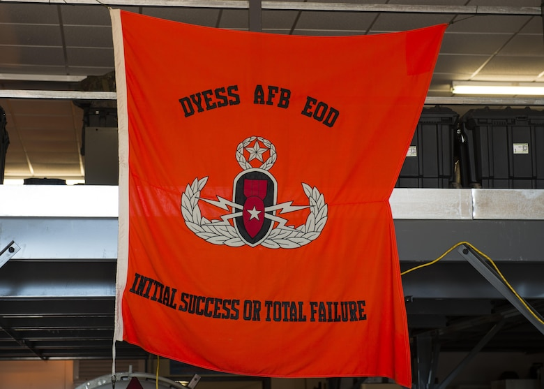 "A flag reading the explosive ordnance disposal motto, ""Initial success or total failure"", hangs from the ceiling of the 7th Civil Engineer Squadron EOD flight building at Dyess Air Force Base, Texas, June 28, 2017. EOD Airmen are tasked to identify, locate and if necessary, defuse any explosives that may pose a threat to the base and its assets. (U.S. Air Force photo by Senior Airman Katherine Miller)"