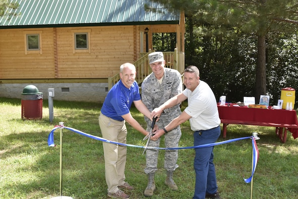John McKelvey, Arnold Air Force Base Services Branch, AEDC Commander Col. Rodney Todaro and David Wilhite, Arnold AFB Civil Engineering Branch, cut the ribbon at the grand opening and ceremony June 20, 2017 for the Dogwood Ridge recreation area at Arnold Air Force Base. Dogwood Ridge has four fully equipped cabins with access to Woods Reservoir shore and beach area. Each cabin has heat and air, a kitchenette, bathroom, downstairs and loft bedroom, living room, and dining area. All cabins have a double bed, two twin beds and a futon which folds out to a double bed. (U.S. Air Force photo/Rick Goodfriend)