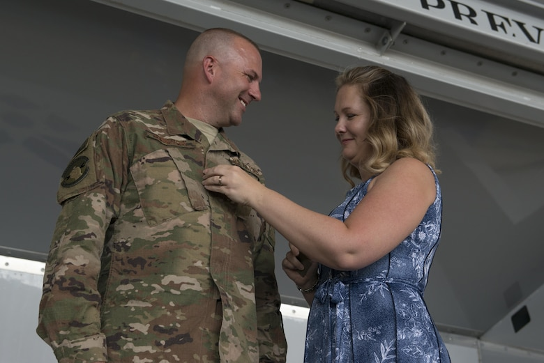 Lt. Col. Christopher Dunston, 723d Aircraft Maintenance Squadron commander, is tacked on by his wife during a promotion ceremony June 28, 2017, at Moody Air Force Base, Ga. During the ceremony, Chris promoted to lieutenant colonel and his younger cousin, then Senior Master Sgt. Brandon Dunston, 74th Aircraft Maintenance Unit superintendent, promoted to chief master sergeant. (U.S. Air Force photo by Airman 1st Class Lauren M. Sprunk)