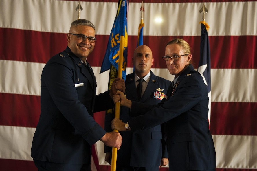 U.S. Air Force Lt. Col. Wendie Mount, prior 316th Training Squadron Commander, passes the unit guideon to Col. Alejandro Ganster, 17th Training Group Commander, during the 316th TRS Change of Command at the Fire Academy high bay on Goodfellow Air Force Base, Texas, June 30, 2017. Mount served as the 316th TRS Commander from 2015 to 2017.  (U.S. Air Force photo by Senior Airman Scott Jackson/Released)