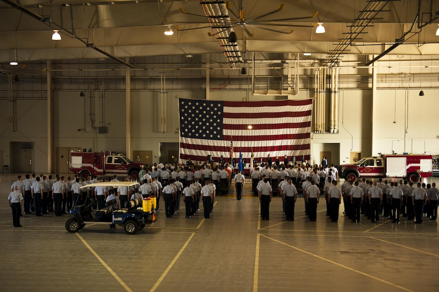 The 316th Training Squadron and visitors stand for the singing of the National Anthem during the 316th TRS Change of Command ceremony at the Fire Academy high bay on Goodfellow Air Force Base, Texas, June 30, 2017. The ceremony bade farewell to  the previous commander, Lt. Col. Wendie Mount and welcomed the new commander, Lt. Col. Robert Kammerer. (U.S. Air Force photo by Senior Airman Scott Jackson/Released)