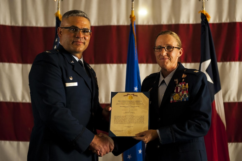 U.S. Air Force Col. Alejandro Ganster, 17th Training Group Commander, awards Lt. Col. Wendie Mount the Air Force Meritorious Service 5th oak leaf cluster medal during the 316th TRS Change of Command ceremony at the Fire Academy high bay on Goodfellow Air Force Base, Texas, June 30, 2017. Mount served as the 316th TRS Commander from 2015 to 2017.  (U.S. Air Force photo by Senior Airman Scott Jackson/Released)
