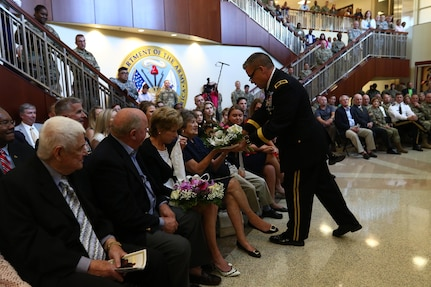 Brig. Gen. Michael Warmack, Chief of Army Reserve Command Operations, Plans and Training, presents his mother, Toni, with a bouquet of flowers during his retirement ceremony at Fort Bragg, N.C., June 29, 2017. Warmack honored his wife and parents during the ceremony, especially his mother, Toni, who he credits as being an instrumental part of his life. (U.S. Army Reserve photo by Staff Sgt. Felix R. Fimbres)