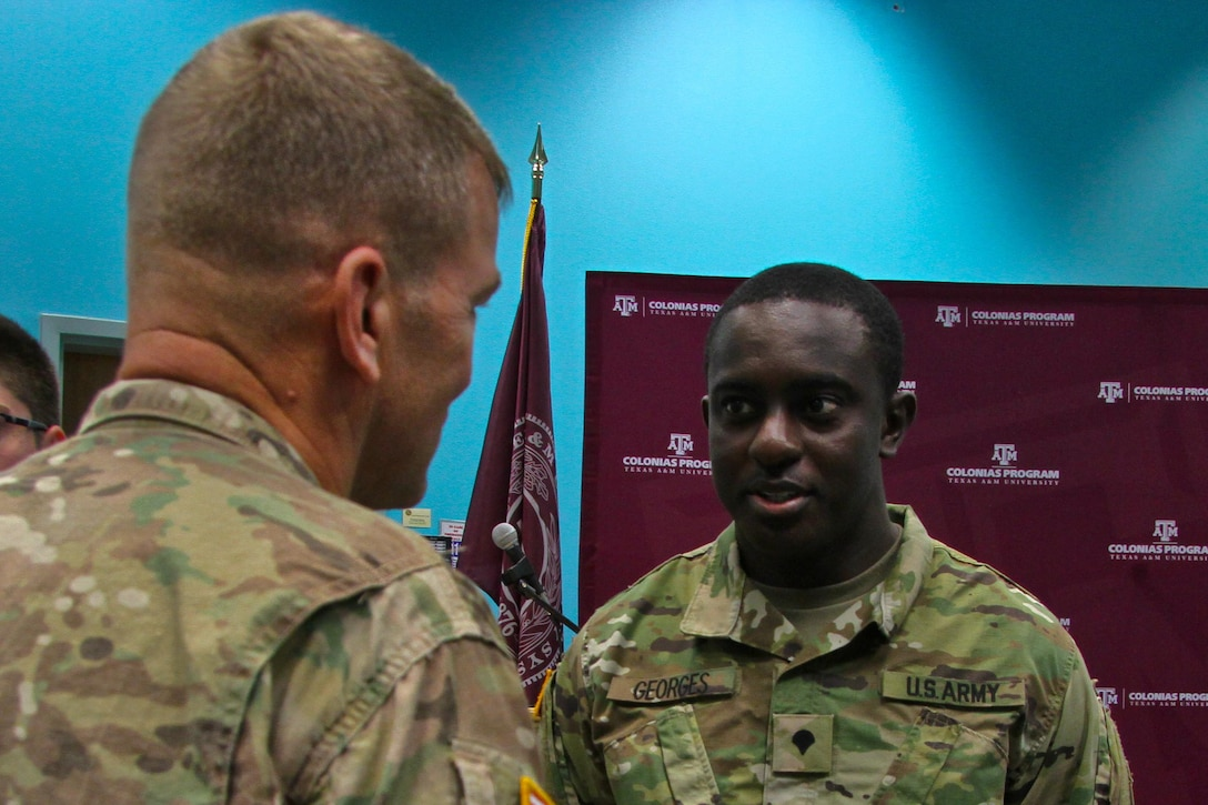 Spc. Daniel Georges, a civil affairs specialist with 478th Civil Affairs Battalion, informs Lt. Gen. Jeffrey S. Buchanan, commander of U.S. Army North (Fifth Army), about his duties during the Innovative Readiness Training (IRT) Mission in Laredo, Texas, June 27. (Photo by Staff Sgt. Tomora Nance, U.S. Army North Public Affairs)