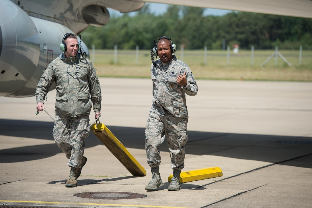 Tech. Sgt. Jordan Wright and Senior Master Sgt. Alphonzo Glover, both maintenance Reservists from the 513th Air Control Group, pull chocks from an E-3 Sentry Airborne Warning and Control System aircraft on June 7, 2017, at NATO Air Base Geilenkirchen, Germany, prior to a mission in support of BALTOPS 2017. Both Airmen are a part of the nearly 100 Reservists supporting the BALTOPS 2017 exercise, which involves 50 ships and submarines and 40 aircraft from 14 member nations. (U.S. Air Force photo/2nd Lt. Caleb Wanzer)