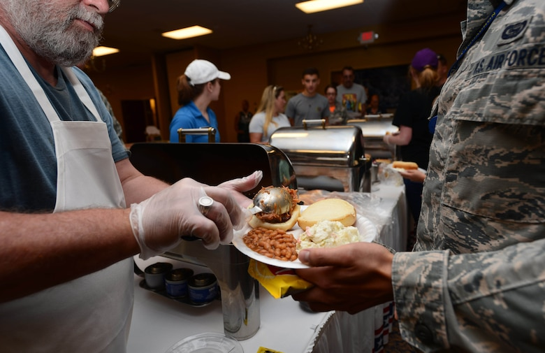 An Airman serves food in the Dakota's Club during the annual base picnic at Ellsworth Air Force Base, S.D., June 30, 2017. During the picnic, families were served hotdogs, pulled pork sandwiches, coleslaw, beans and chips as well as a variety of drinks. (U.S. Air Force photo by Airman 1st Class Donald C. Knechtel)