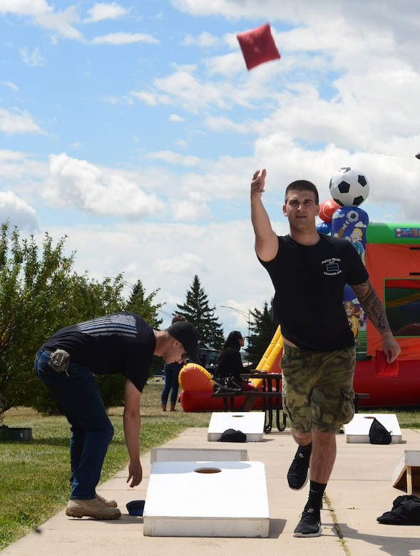 Airmen play a game of bean bag toss during the annual base picnic at Ellsworth Air Force Base, S.D., June 30, 2017. The event included a variety of activities for Airmen and their families to participate in including paintball, bubble soccer and bounce houses for children. (U.S. Air Force photo by Airman 1st Class Donald C. Knechtel)