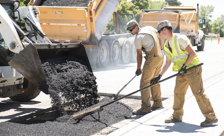 Airman Austin Eisele (left) and Senior Airman Andrew-David Dalton (right), 366th Civil Engineer Squadron Dirtboys, work alongside one another while laying asphalt at Mountain Home Air Force Base, Idaho, June 14, 2017. Part of the responsibility of the Dirtboys is to reconstruct unserviceable roads. (U.S. Air Force photo by Senior Airman Jessica H. Smith/Released)