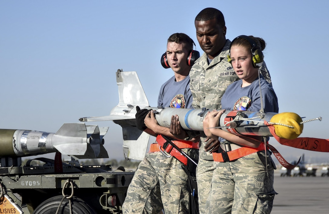 Airmen from the 57th Maintenance Group transport a missile during a load crew competition at Nellis Air Force Base, Nev., June 30, 2017. Squadrons from around the 57th Wing compete against each other to see who can most accurately and quickly arm an aircraft. (U.S. Air Force photo by Airman 1st Class Andrew D. Sarver/Released)