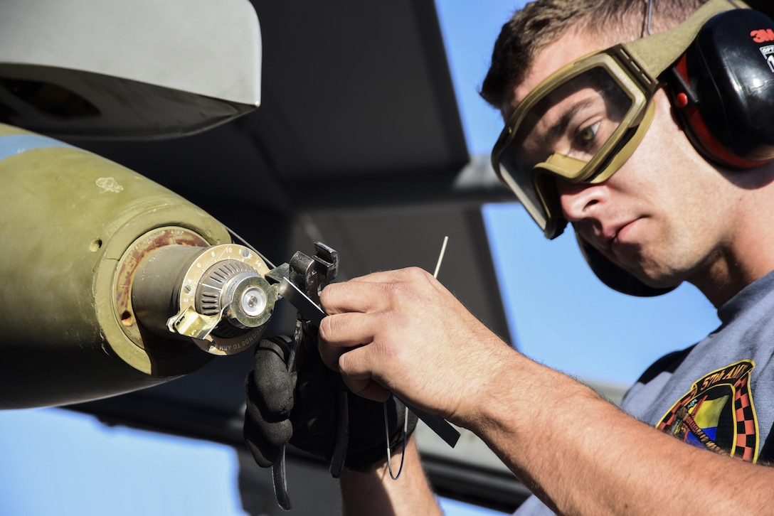 An Airman from the 57th Maintenance Group secures a bomb to an F-16 Fighting Falcon, assigned to the 16th Weapons Squadron, during a load crew competition June 30, 2017, at Nellis Air Force Base, Nev. Each team was tested on their timeliness and accuracy while loading and unloading munitions on their aircraft. (U.S. Air Force photo by Airman 1st Class Andrew D. Sarver/Released)