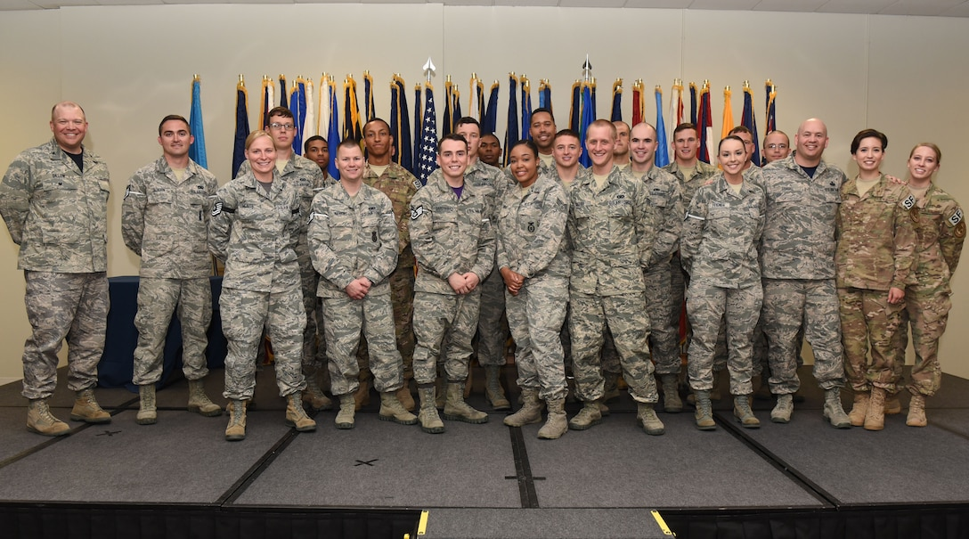 Col. Matthew Dillow, 90th Missile Wing vice commander and Chief Master Sgt. Jeffery Steagall, 90th MW command chief pose for a group photo with enlisted Airmen who promoted in June during the wing promotion ceremony at F.E. Warren Air Force Base, Wyo., June 30, 2017. Each month the Mighty Ninety hosts a ceremony to recognize the promotees from the base. (U.S. Air Force photo by Airman 1st Class Breanna Carter)