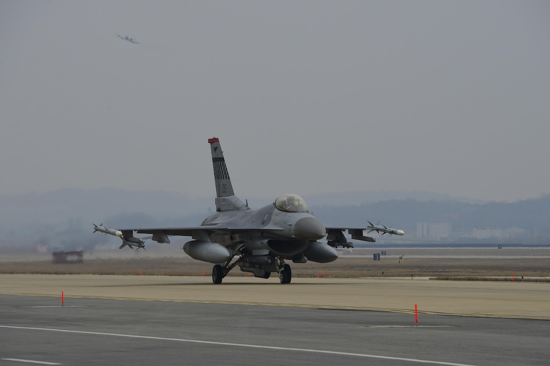 An F-16 Fighting Falcon assigned to the 36th Fighter Squadron taxis to the runway for a training mission while an A-10 Thunderbolt II from the 25th Fighter Squadron takes off during Exercise Beverly Herd 17-1 at Osan Air Base, Republic of Korea, March 1, 2017. Pilots from both fighter squadrons flew multiple sorties during exercise Beverly Herd, honing their flying skills and ability to work around the rugged ROK landscape. (U.S. Air Force photo by Staff Sgt. Victor J. Caputo)