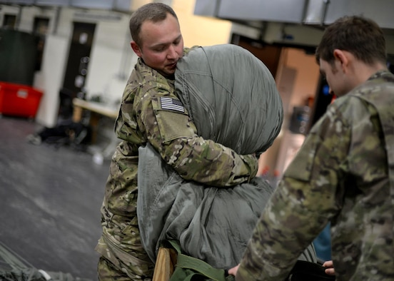 U.S. Air Force Staff Sgt. Brian Demik, left, and U.S. Air Force Staff Sgt. Nicholas Brunjes, both 352d Special Operations Support Squadron aerial delivery riggers, pack a parachute Feb. 15, 2017, on RAF Mildenhall, England. Rigger pack a variety of parachutes, including 28-feet, 26-feet and 15-feet chutes, 68-inch pilot parachutes, (small, auxiliary parachute used to deploy the main or reserve), and G-12 Army parachutes, along with drogues and sandbags. (U.S. Air Force photo by Senior Airman Christine Halan)