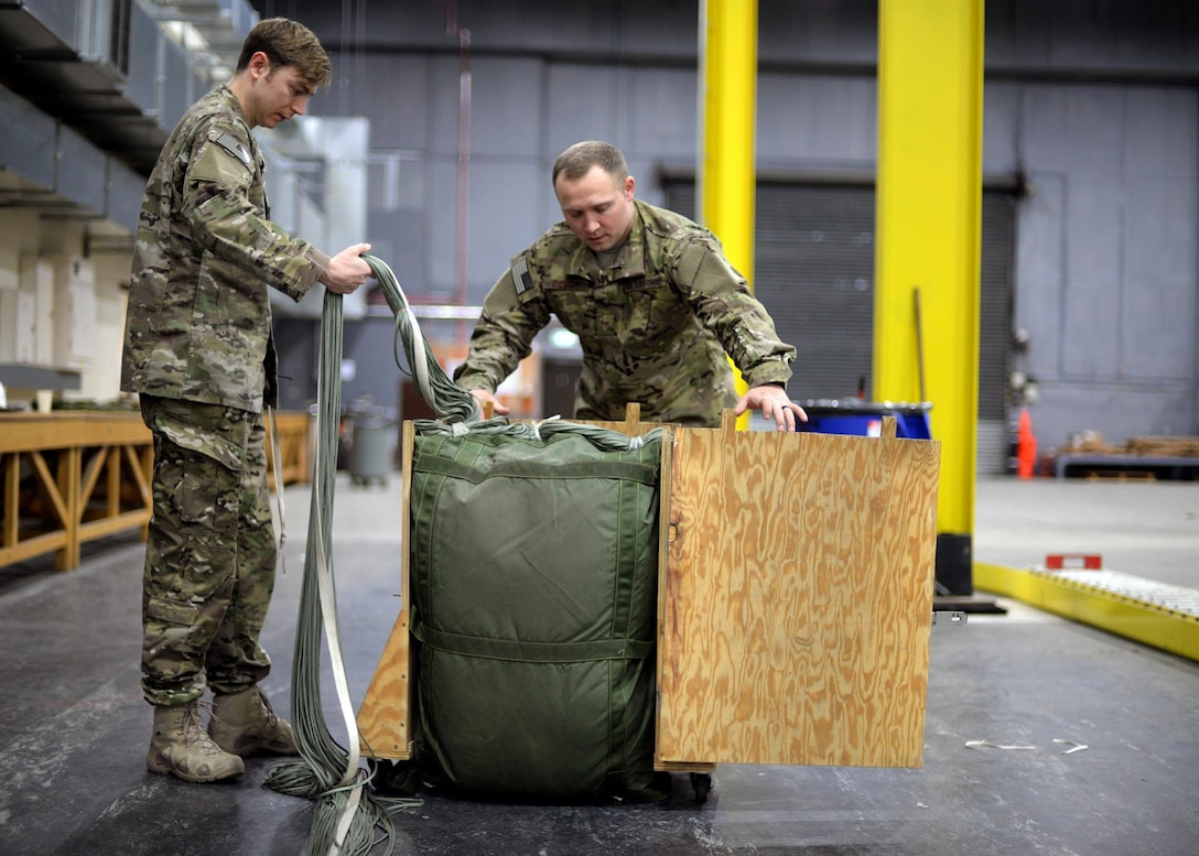 U.S. Air Force Staff Sgt. Nicholas Brunjes, left, and U.S. Air Force Staff Sgt. Brian Demik, both 352d Special Operations Support Squadron Aerial Delivery riggers, complete the process of packing a parachute Feb. 15, 2017, on RAF Mildenhall, England. Rigger pack a variety of parachutes, including 28-feet, 26-feet and 15-feet chutes, 68-inch pilot parachutes, (small, auxiliary parachute used to deploy the main or reserve), and G-12 Army parachutes, along with drogues and sandbags. (U.S. Air Force photo by Senior Airman Christine Halan)