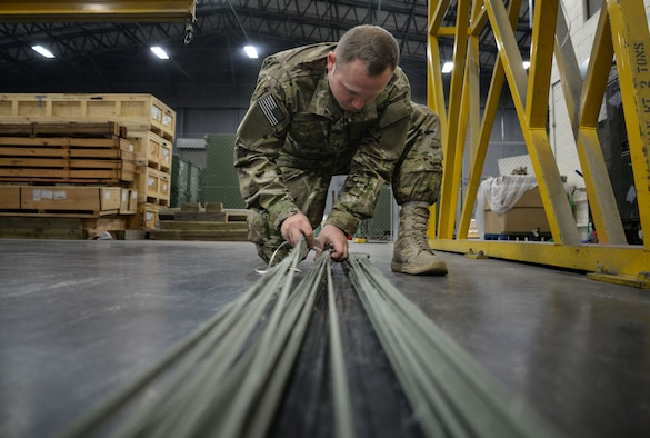 U.S. Air Force Staff Sgt. Brian Demik, 352d Special Operations Support Squadron aerial delivery rigger, untangles parachute cords Feb. 15, 2017, on RAF Mildenhall, England. The aerial delivery flight have the capability of sewing the parachutes for on the spot repairs, anytime there is a hole, tear or friction burn. (U.S. Air Force photo by Senior Airman Christine Halan)