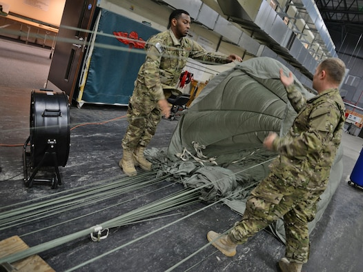 U.S. Air Force Staff Sgt. Jarryd Dooley, left, and U.S. Air Force Staff Sgt. Brian Demik, both 352d Special Operations Support Squadron Aerial Delivery riggers, untangle a parachute Feb. 15, 2017, on RAF Mildenhall, England. The aerial delivery flight uses industrial vehicles to collect the cargo after it's been dropped from the aircraft. (U.S. Air Force photo by Senior Airman Christine Halan)