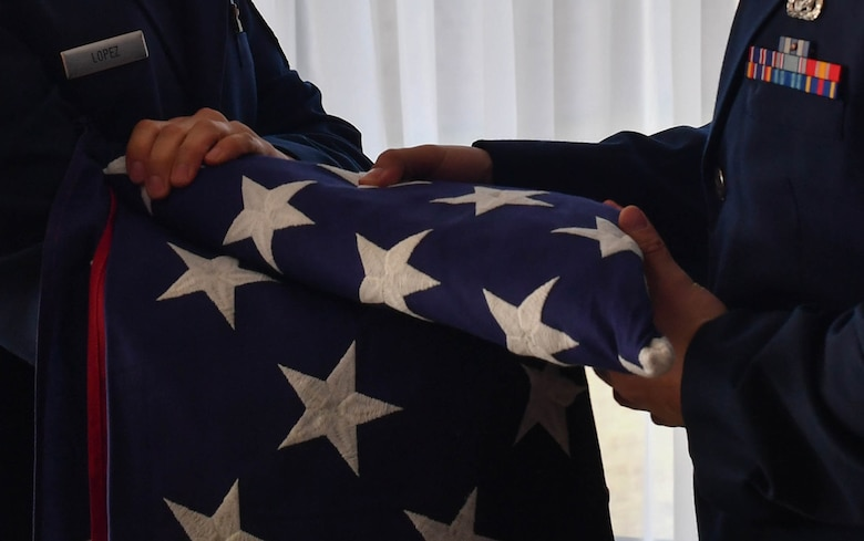Master Sgt. Henry Lopez, U.S. Air Forces in Europe readiness and plans manager, and Senior Airman Zachary Abraham, 435th Security Forces Squadron commander's support staff, fold an American flag during a dual retirement ceremony on Ramstein Air Base, Germany, Feb. 24, 2017. With at least 40 years of service each, John and Colynn Hamilton, USAFE management analyst and human resources specialist respectively, retired to spend time with their five kids and 12 grandchildren. (U.S Air Force photo by Senior Airman Tryphena Mayhugh)