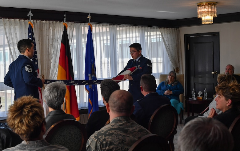 Master Sgt. Henry Lopez, U.S. Air Forces in Europe readiness and plans manager, and Senior Airman Zachary Abraham, 435th Security Forces Squadron commander's support staff, fold an American flag during a dual retirement ceremony on Ramstein Air Base, Germany, Feb. 24, 2017. John and Colynn Hamilton, USAFE management analyst and human resources specialist respectively, as well as husband and wife, retired after more than 80 years of combined service. (U.S Air Force photo by Senior Airman Tryphena Mayhugh)