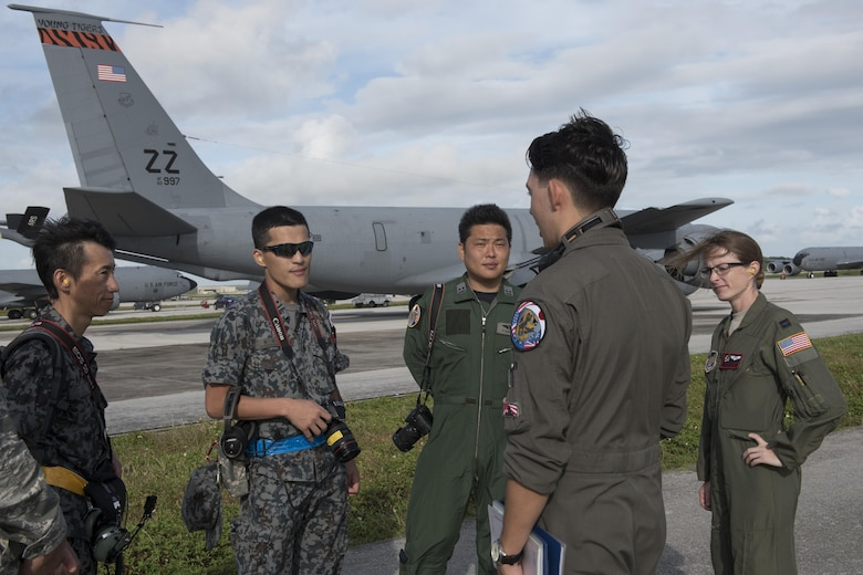 U.S. Air Force Airman 1st Class Luke Story, 909th Air Refueling Squadron boom operator, prepares to conduct aerial refueling while being observed by Japan Air Self-Defense Force 1st Lt. Yoshifumu Takase March 1, 2017, off the coast of Guam. The refueling was conducted for exercise Cope North, an annual gathering of Japanese, U.S. and Australian service members who train to increase combat readiness and interoperability. (U.S. Air Force photo by Senior Airman John Linzmeier)