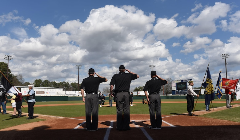 Umpires render salutes during the National Anthem at the Freedom Classic baseball series, Feb. 25, 2017, at Grainger Stadium in Kinston, North Carolina. The U.S. Air Force Academy beat the U.S. Naval Academy 2-1 in the series. (U.S. Air Force photo by Airman Miranda A. Loera)