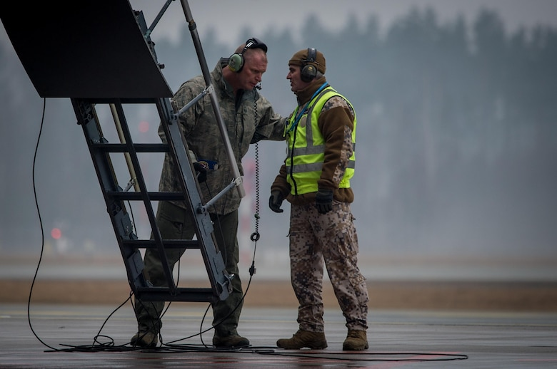 A U.S. Air Force crew chief and a Latvian soldier coordinate unloading a C-5M Super Galaxy at Riga International Airport, Latvia, Mar. 1, 2017, where it delivered UH-60 Black Hawk helicopters for the U.S. Army in support of Operation Atlantic Resolve. Five Black Hawk helicopters will be deployed to Latvia as part of a larger contingent of helicopters and personnel deployed to support Operation Atlantic Resolve, a U.S. commitment to maintaining peace and stability in the European region. (U.S. Air Force photo/Tech. Sgt. Ryan Crane)