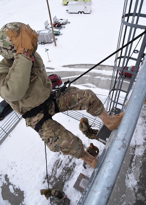 Airman Keegan Okland-Kenney (right) and Airman Bradley Novack descend the 30 foot wall during rappelling exercises Feb. 25 at the Cheyenne Fire Department training facility. The rappelling course is designed to train future Tactical Response Force members how to properly rappel to descend quickly into a launch facility in case of emergency. (U.S. Air Force Photo by Glenn S. Robertson)