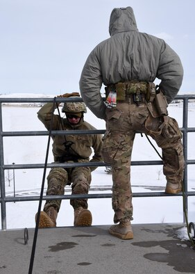 Airman 1st Class Steven Berard belays for another classmate descending the 70 foot wall during rappelling exercises Feb. 25 at the Cheyenne Fire Department training facility. The belaying position is a safety position to ensure the Airman who is rappelling has someone supporting a controlled decline. The rappelling course is designed to train future Tactical Response Force members how to properly rappel to descend quickly into a launch facility in case of emergency. (U.S. Air Force Photo by Glenn S. Robertson)