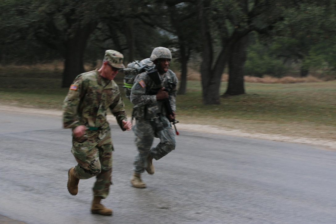 Medical Readiness and Training Command's Command Sgt. Maj. Ian Coyle runs with Sgt. Terrelle Fields, Northeast Medical Area Readiness Support Group, who leads the pack during the ruck march event of the Best Warrior Competition at Camp Bullis, Texas, 11 Feb. Fields was the first competitor to complete the 4-mile march, doing so in 45:03.  Soldiers from the MRTC, Northeast MARSG, Southeast MARSG, Central MARSG and Western MARSG competed in the Best Warrior Competition for their respective commands at Camp Bullis, Texas, 8-12 Feb., 2017.