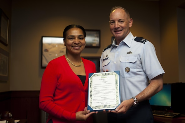Qiana Woods, 17th Force Support Squadron Airman and Family Readiness Center work-life consultant, and Col. Michael Downs, 17th Training Wing Commander, present the Military Saves memorandum of understanding in the Norma Brown building on Goodfellow Air Force Base, Texas, February 28, 2017. Month of Military Saves is a campaign dedicated to encouraging military members to save money and set financial goals. (U.S. Air Force photo by Senior Airman Scott Jackson/Released)