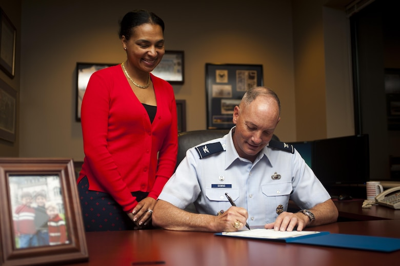 Qiana Woods, 17th Force Support Squadron Airman and Family Readiness Center work-life consultant, watches Col. Michael Downs, 17th Training Wing Commander, sign the Military Saves memorandum of understanding in the Norma Brown building on Goodfellow Air Force Base, Texas, February 28, 2017. Downs' financial goal is to save towards retirement and a home. (U.S. Air Force photo by Senior Airman Scott Jackson/Released)