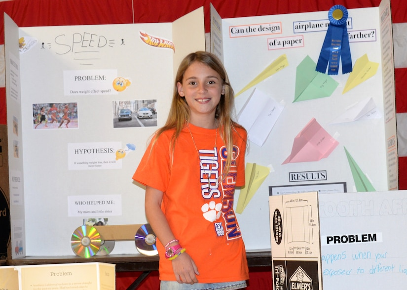 """Savannah Altine, 11, a fourth-grade student at Marrington Elementary (MNE) School, located at Joint Base Charleston – Weapons Station, poses in front of her science fair project following the MNE Science Fair Feb. 21. Altine earned """"First Prize"""" for her project, """"Can the Design of a Paper Airplane Make it Go Farther?"""""""