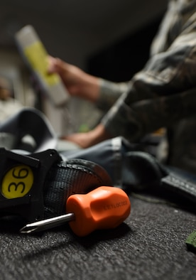 U.S. Air Force Airman 1st Class Femylyn Plan, 1st Operation Support Squadron aircrew flight equipment technician, inspects flight equipment at Joint Base Langley-Eustis, Va., Feb. 27, 2017. The technicians inspect equipment ranging from communication to life-saving gear required for pilots in order to have a successful flight. (U.S. Air Force photo by Staff Sgt. Natasha Stannard)