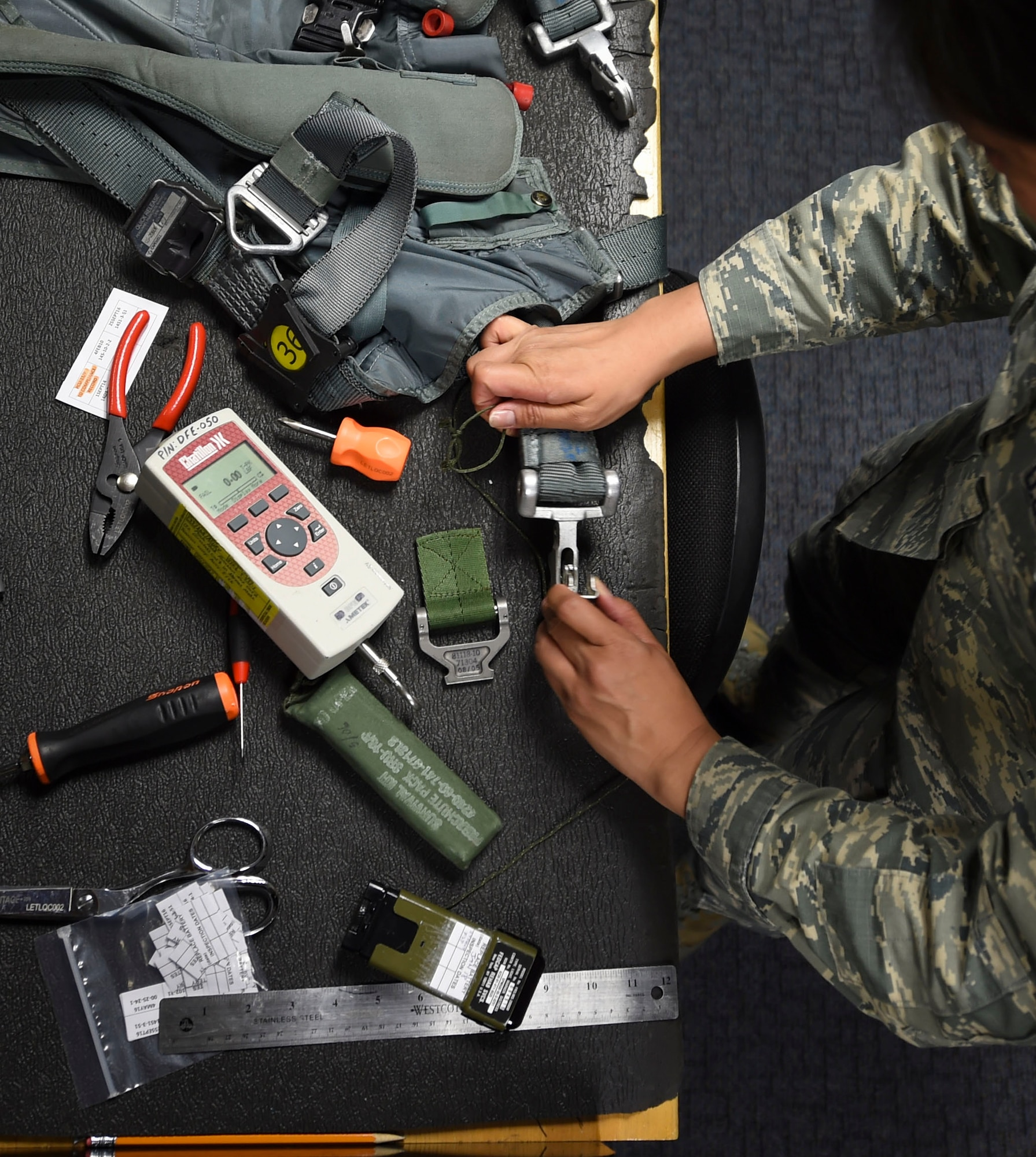 U.S. Air Force Airman 1st Class Femylyn Plan, 1st Operation Support Squadron aircrew flight equipment technician, repairs a parachute harness at Joint Base Langley-Eustis, Va., Feb. 27, 2017. The harness attaches to the parachute, securing a pilot to the chute in an emergency egress. (U.S. Air Force photo by Staff Sgt. Natasha Stannard)