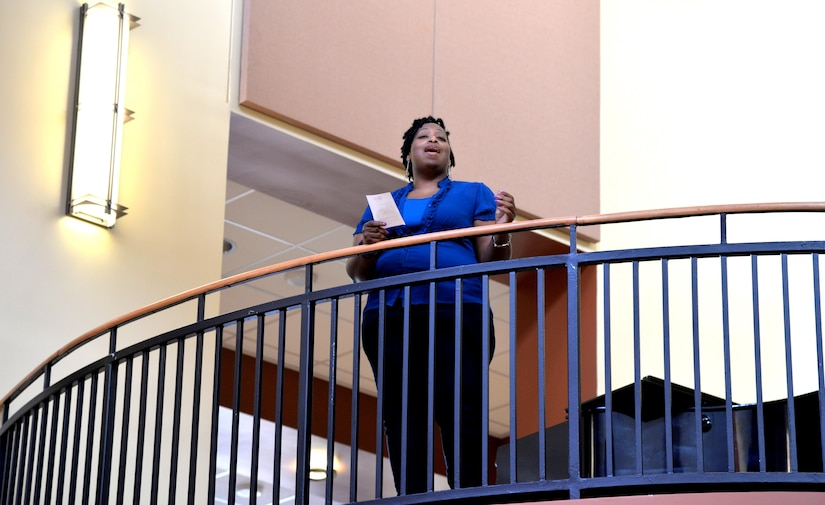 """Kimberly Humphrey, poet and author of """"Dear Black Men: I Love You,"""" recites her poem, """"What do you see?,"""" from a balcony at Naval Health Clinic Charleston Feb. 24 during NHCC's Black History Month observance. Humphrey is a Navy veteran and a government employee, currently residing in the Lowcountry."""