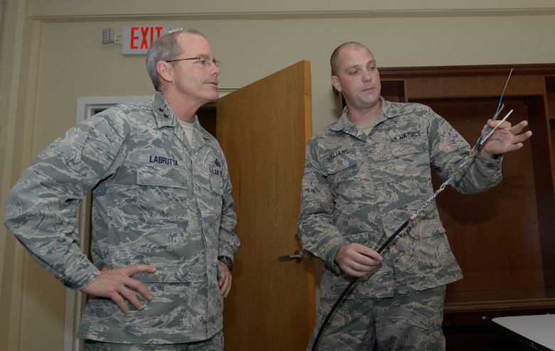 Senior Airman Micheal Turland, 85th Engineering Installation Squadron cable and antenna systems technician, explains opening up fiber optic cable to Maj. Gen. Robert LaBrutta, 2nd Air Force commander, during a 2nd AF immersion tour of the unit located at Keesler Air Force Base, Miss., Feb. 9, 2017. The Airmen at the 85th EIS are part of the only active duty EIS in the Air Force. They are also the only organization in the Defense Department providing specialized engineering services such as electromagnetic hazard and interference investigations and High Altitude Electromagnetic Pulse protection. (U.S. Air Force photo by Andre' Askew)