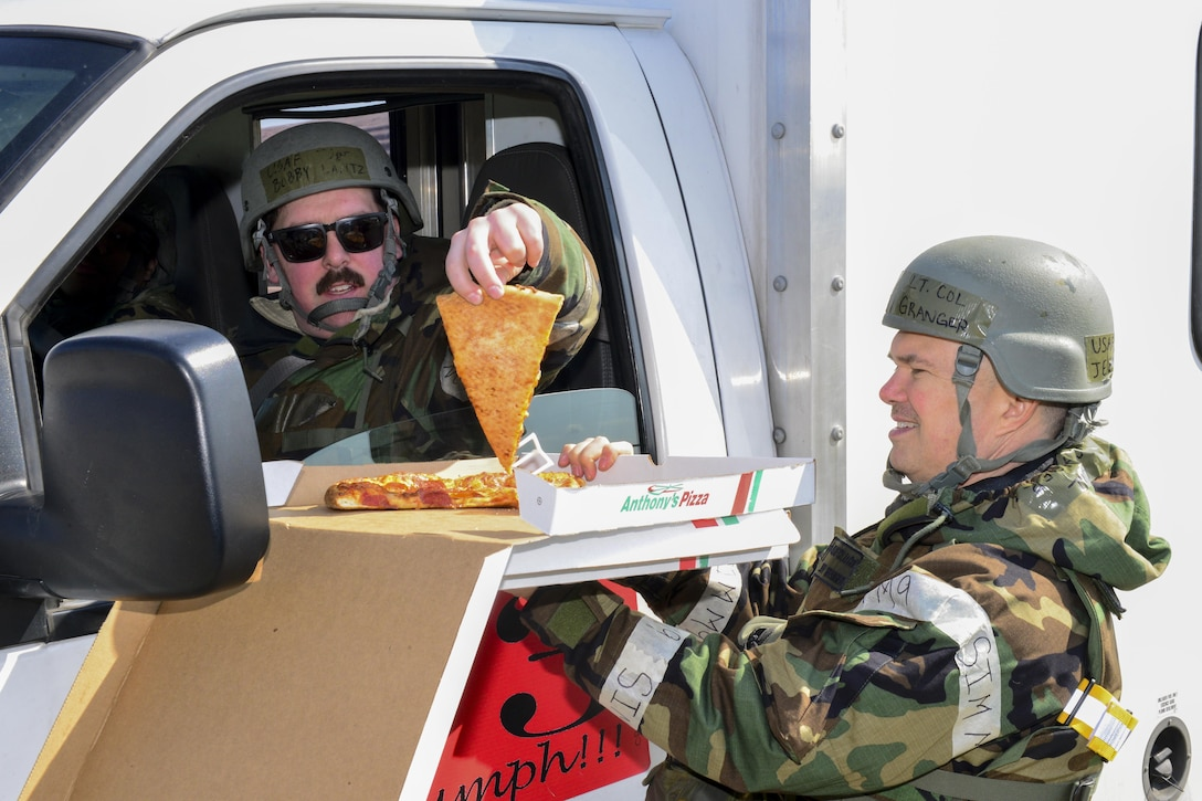 U.S. Air Force Chap. (Lt. Col.) Jeffrey Granger, 51st Fighter Wing wing chaplain, gives U.S. Air Force Tech. Sgt. Robert Lantz, 51st Aircraft Maintenance Squadron, a slice of pizza during Exercise Beverly Herd 17-1 at Osan Air Base, Republic of Korea, March 2, 2017. The wing chapel staff made morale visits to different units across the base, bringing free food and drink with them wherever they went. (U.S. Air Force photo by Staff Sgt. Victor J. Caputo)