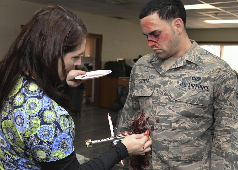 """Jamie Gujski, 51st Medical Group education and training simulation operator, prepares a role player as a simulated unexploded ordnance victim during Exercise Beverly Herd 17-1 at Osan Air Base, Republic of Korea, March 2, 2017. The scenario was based off of a real-world situation that happened in the Middle East, painting a realistic picture of war that highlighted the importance of being prepared and ready to """"Fight Tonight."""" (U.S. Air Force photo by Airman Gwendalyn Smith)"""