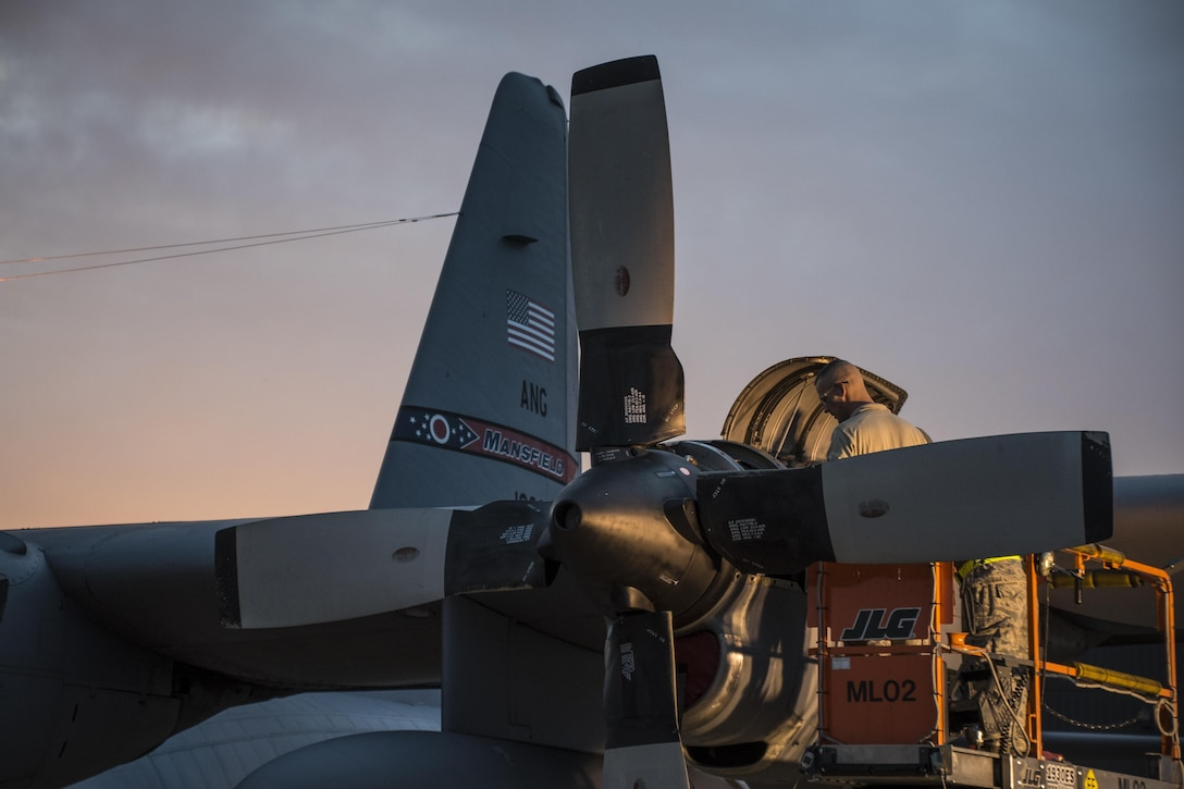 179th Airlift Wing Maintenance members work on the engine of a C-130H Hercules as the sun rises, Feb. 21, 2017, at the 179th Airlift Wing, Mansfield, Ohio.  The 179th Airlift Wing is always on mission to be the first choice to respond to community, state and federal missions with a trusted team of highly qualified Airmen. (U.S. Air National Guard photo by 1st Lt. Paul Stennett/Released)
