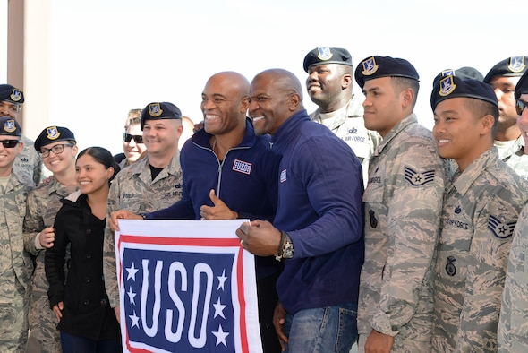 "Mixed martial arts fighter Anderson Silva (left) and actor Terry Crews pose for a photo with Airmen from the 412th Security Forces Squadron. The squadron put on a military working dog demonstration as part of the stars' visit Feb. 24 to introduce the new Netflix show ""Ultimate Beastmaster."" (U.S. Air Force photo by Kenji Thuloweit)"