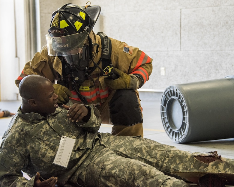 A firefighter with the 96th Civil Engineer Group, checks the condition of a U.S. Army 7th Special Forces Group (A)  participant during an exercise Feb. 23 at Eglin Air Force Base, Fla. The simulated detonation scenario tested firefighters, security forces and medical emergency response personnel agencies among others. (U.S. Air Force photo/Ilka Cole)