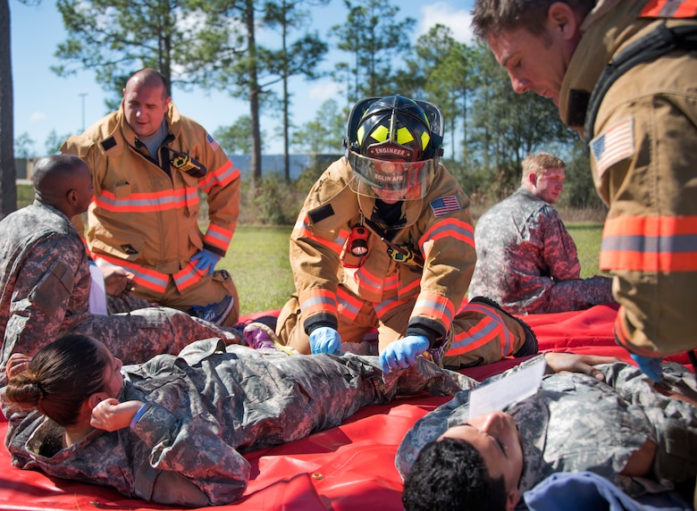 Firefighters with the 96th Civil Engineer Group, evaluate and treat U.S. Army 7th Special Forces Group (A) participants after a simulated decontamination process Feb. 23 during an exercise at Eglin Air Force Base, Fla. The simulated detonation scenario tested firefighters, security forces and medical emergency response personnel agencies among others. (U.S. Air Force photo/Ilka Cole)