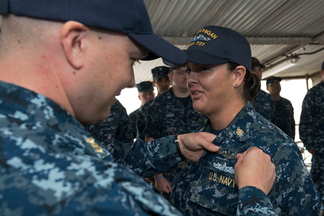 Navy Chief Petty Officer Dominique Saavedra is pinned with her enlisted submarine qualification during a ceremony