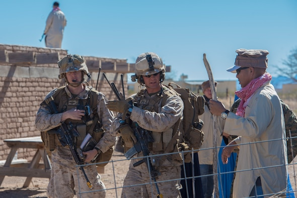 A Marine from the I Marine Expeditionary Force assigned to Marine Corps Base Camp Pendleton, Calif., asks a mock Southwest Asian local in a bazaar about the whereabouts of a downed aircrew during a simulated Tactical Recovery of Aircraft and Personnel scenario, Feb 22, 2017, at the Playas Training and Research Center, N.M. During the scenario, the IMEF rescued isolated personnel from a downed aircraft while fending off mock opposition forces from Davis-Monthan Air Force Base, Ariz.'s 563d Operations Support Squadron. This joint effort prepared the IMEF by completing their Special Purpose Marine Air Ground Task Force certification. This is the culmination of their crisis response operations before deploying to the United States Central Command, which consists of 20 countries In Northeast Africa and Southwest Asia. (U.S. Air Force photo by Airman 1st Class Greg Nash)