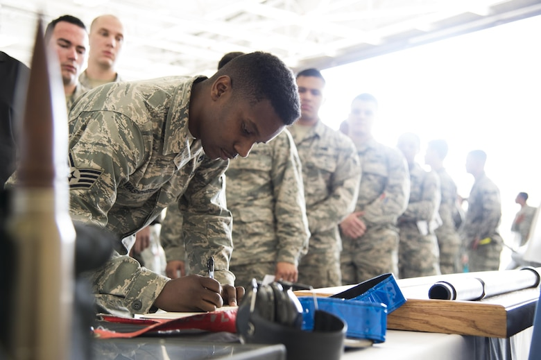 Staff Sgt. Tayrell Washington, 23d Maintenance Group weapons standardization lead crew team chief, signs a guestbook during a memorial ceremony in honor of Staff Sgt. Sara Toy, 74th Aircraft Maintenance Unit weapons team chief, March 1, 2017, at Moody Air Force Base, Ga. Toy, a New Kent, Virginia native, died in a car accident Feb. 25, 2017. During the ceremony, she was remembered as a valuable member of the Team Moody weapons community and was posthumously awarded the Air Force Commendation Medal and the rank of Staff Sergeant. (U.S. Air Force photo by Andrea Jenkins/Released)